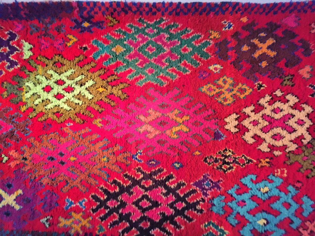 In der Kargheit der marokkanischen Sahara weben Frauen Teppiche und Kissen.